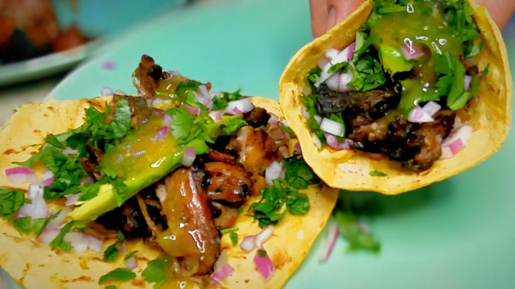 Instant Pot Carnitas flame broiled and stacked on a tortilla with avocado, red onion, cilantro, and salsa verde
