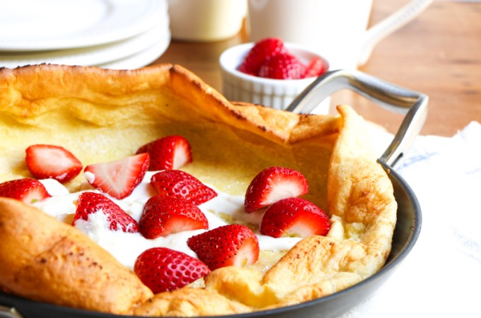 German pancake, also known as a Dutch Baby, with strawberries and sweetened ricotta cheese.
