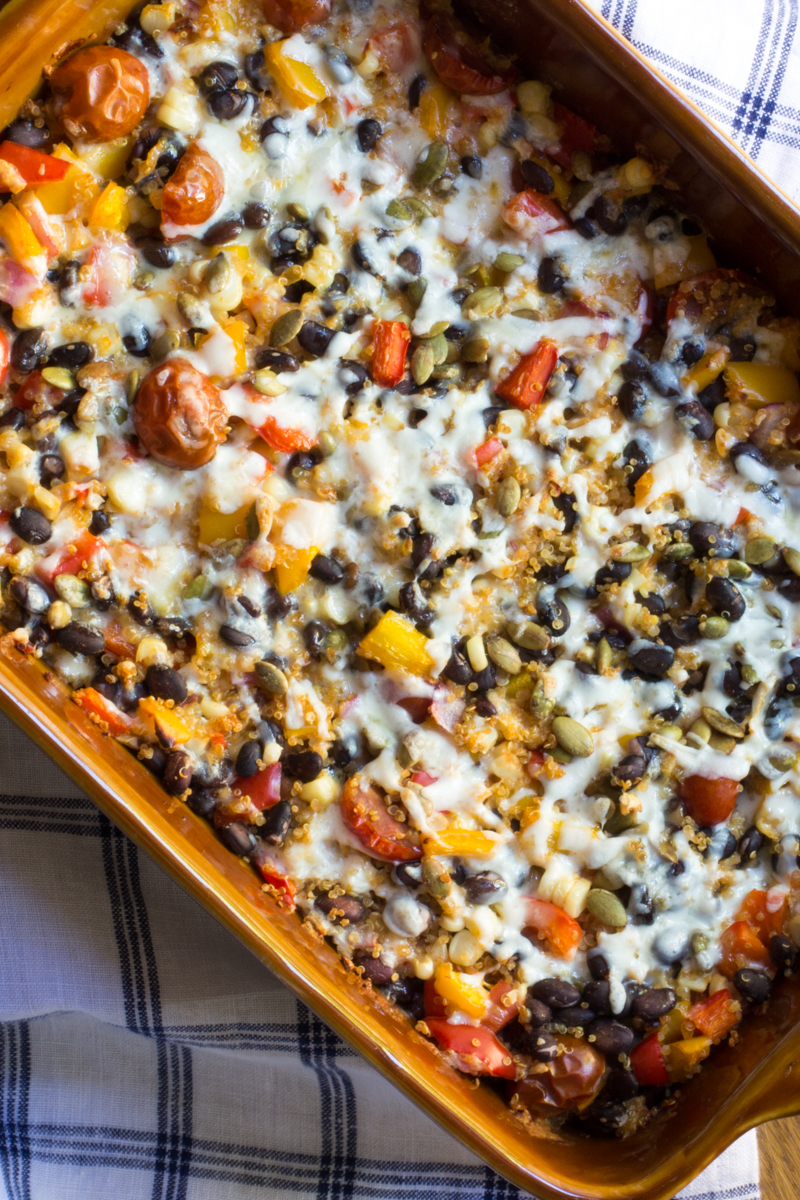 Healthier Mexican casserole with quinoa, black beans, tomatoes, corn, peppers, pumpkin seeds, and cheese.