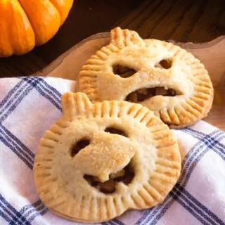 Pumpkin-shaped hand pies filled with apples, ginger, cinnamon and cardamom. Perfect kids treat for Halloween.