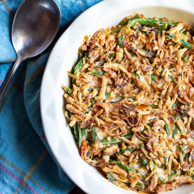 Vegetarian, keto-friendly green bean casserole topped with crispy fried onions. This version of the classic holiday dish adds roasted tomatoes and eliminates the cream of mushroom soup. Only ~27 carbs per serving!