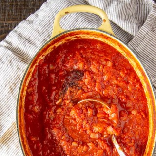This spicy tomato sauce develops layers of flavor from roasting in the oven. It only takes 15 minutes to put together before sliding it into the oven, and can be used for many recipes.