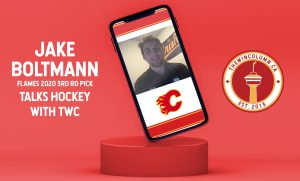 "The Win Column interview with Jake Boltmann, Calgary Flames prospect. The image shows a screenshot of Jake Boltmann during a video interview, with his photo placed in a mockup phone resting on top of a red hockey puck. The title text says ""Jake Boltmann, Flames 2020 3rd Round Pick, Talks Hockey With TWC."""