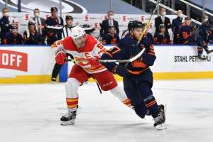 EDMONTON, AB - MAY 1: Connor McDavid #97 of the Edmonton Oilers battles for the puck against Mark Giordano #5 of the Calgary Flames on May 1, 2021 at Rogers Place in Edmonton, Alberta, Canada. (Photo by Andy Devlin/NHLI via Getty Images)