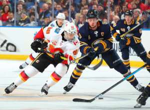 BUFFALO, NY - NOVEMBER 27: Andrew Mangiapane #88 of the Calgary Flames and Jack Eichel #9 of the Buffalo Sabres battle for the puck during an NHL game on November 27, 2019 at KeyBank Center in Buffalo, New York. (Photo by Sara Schmidle/NHLI via Getty Images)