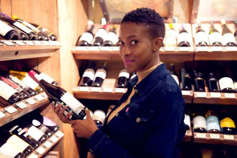 African lady holding a bottle of south african wine