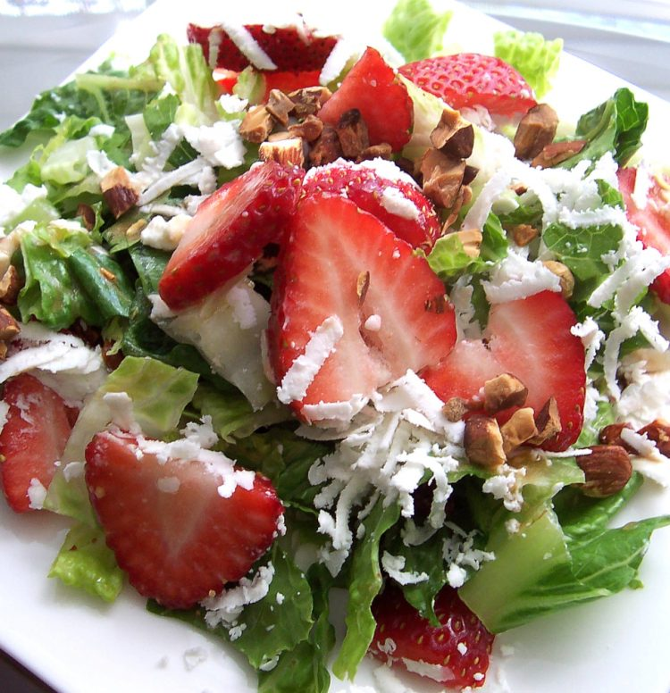 Strawberries and greens drizzled with creamy garlic dressing