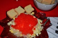 A plate with chopped hard boiled egg topped with sweet onion and red lumpfish caviar.