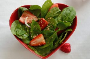 Spinach and strawberry slices in a red hear shaped salad bowl.