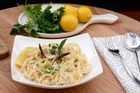 Bowl of Lemoncello Fettuccine on table with fresh oranges and parsley behind.