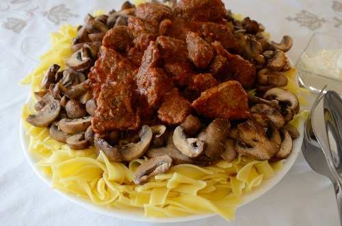 goulash stew on a bed of noodles on a platter