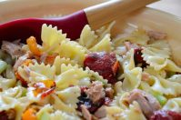 Bow tie pasta with roasted tomatoes and red peppers in a bowl.