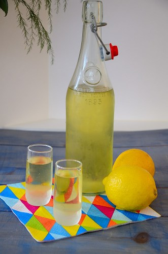 Limoncello bottle with lemons and shot glasses