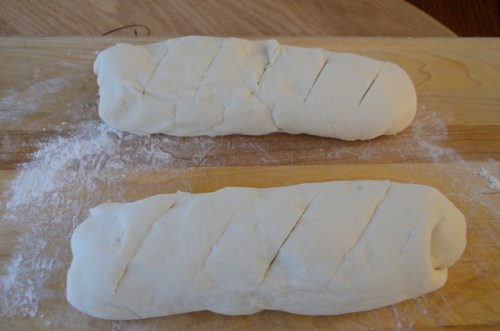 Dough formed into baguette shapes on floured board