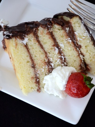 Piece of layer cake on plate with whipped cream and strawberry garnish