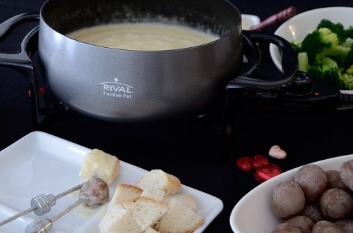 Cheese fondue pot with plate of bread cubes