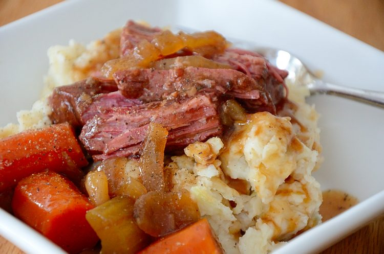 Brisket in Guinness gravy with carrots and celery in a bowl over Colcannon