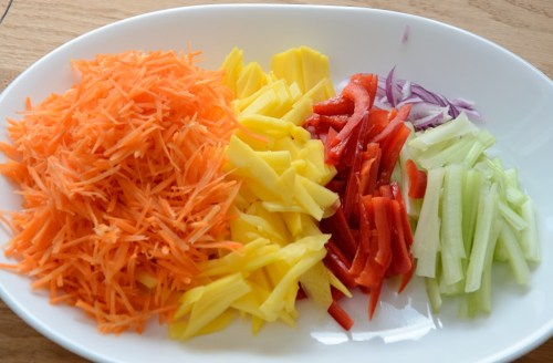 Plate of julienned carrots, mango, pepper and celery