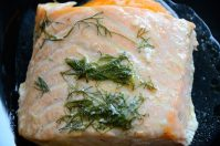 Salmon fillet with fennel fronds and sauce on a a bed or orange slices