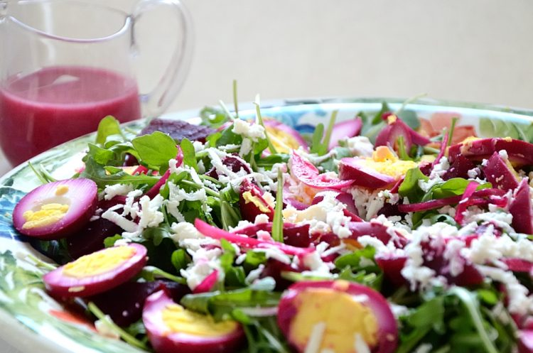 Salad with pickled eggs, beets and feta on a bed of greens