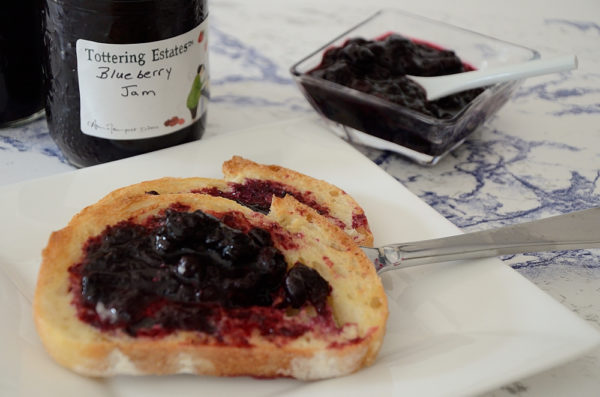 Toast with blueberry jam on a plate with jam jar behind.