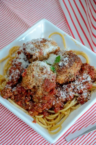 A bowl of spaghetti with 3 meatballs on top