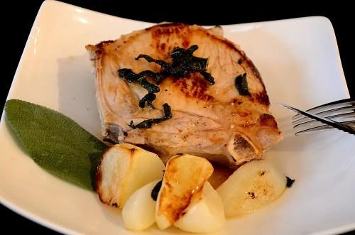 Cider brined pork chop with glazed turnips on a plate