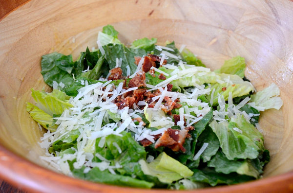 Caesar Salad in a wooden bowl with croutons and grated parmesan garnish