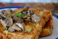Two crispy french toasts on a plate with creamy mushrooms sauce