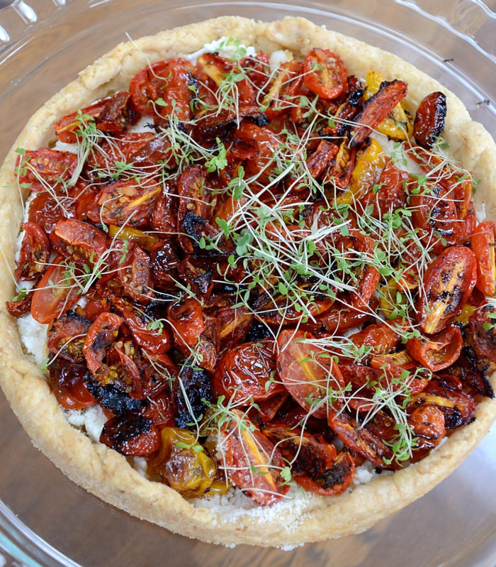 Tart filled with roasted tomatoes and garnished with microgreens