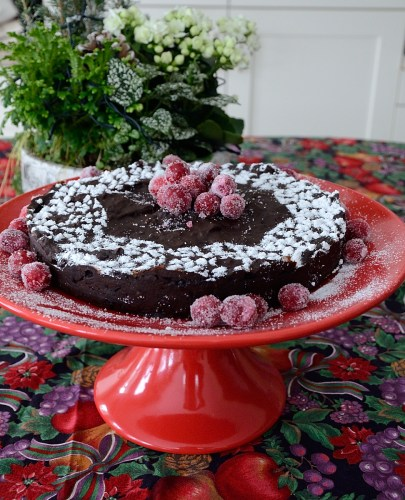 Round brownie cake on a pedestal, with sifted icing sugar and sugared cranberries for garnish