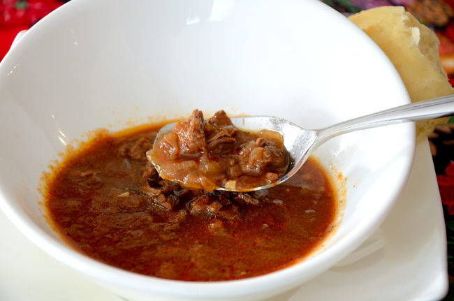 Bowl of goulash soup with a spoonful of broth and beef chunks.