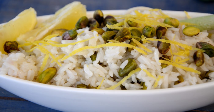 Platter of rice with lemon twists and pistachios garnished with fresh lemon