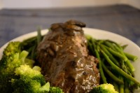 Chateaubriand tenderloin on a platter with broccoli, green beans