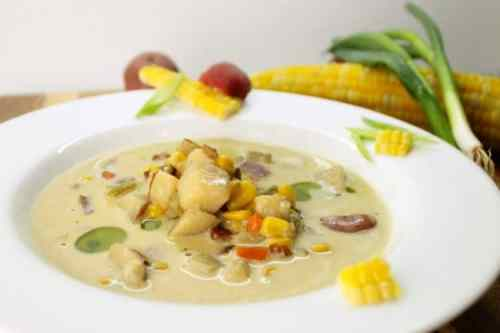 Bowl of creamy chowder with fresh corn and chunks of potato, celery and bacon