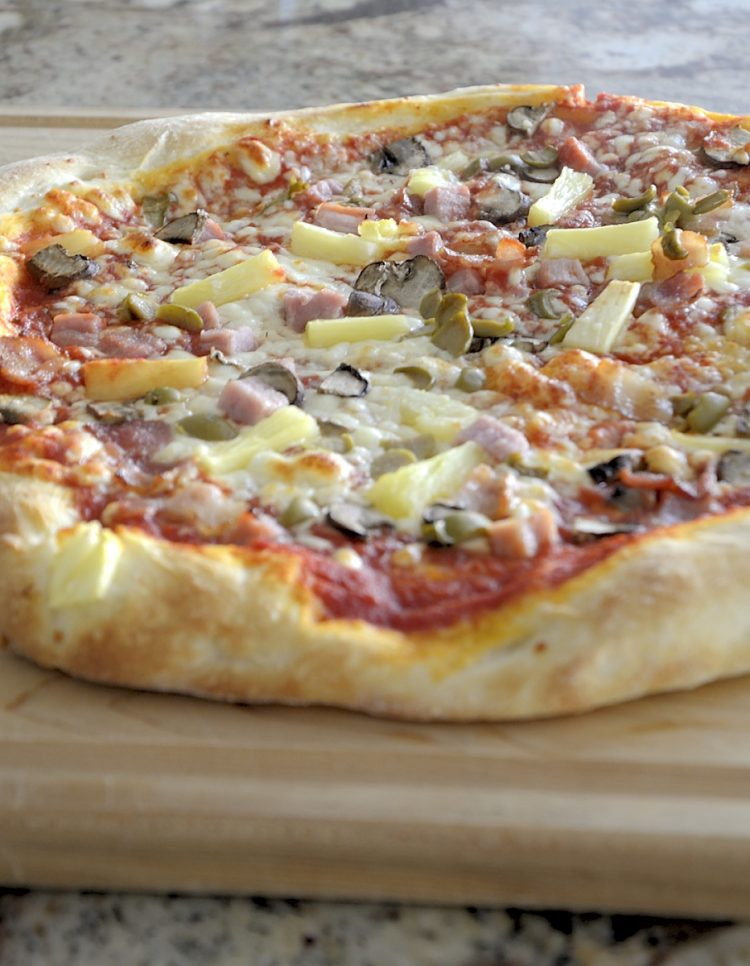 Golden pizza crust with ham and pineapple and melted cheese