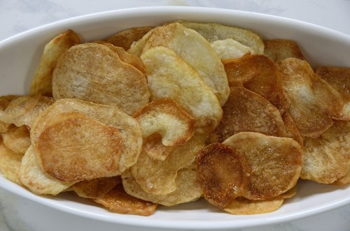 Close up of golden brown potato chips in a dish