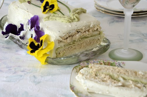 Sliced Chicken Avocado Sandwich cake decorated with purple and yellow pansies, chives for stems and piped avocado mousse for leaves