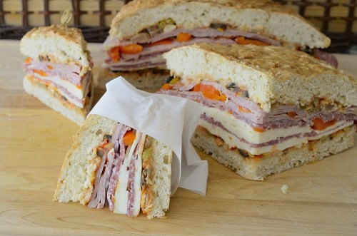 Wedges of muffuletta with cure meats, cheeses and peppers, wrapped in parchment paper