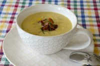 Bowl of thick, creamy corn chowder with bacon and chives