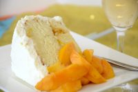 Slice of Peach èn Prosecco cake with whipped cream frosting and fresh peach slices on the side