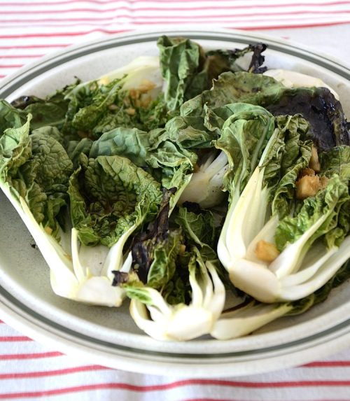 Grilled Baby Bok Choy on a plate with Asian sauce and garlic and ginger