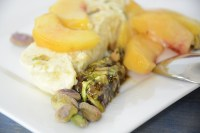 Slice of Semifreddo on a plate garnished with fresh peaches and pistachio brittle.
