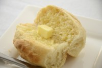 Parker House Roll cut open with a pat of butter in middle.