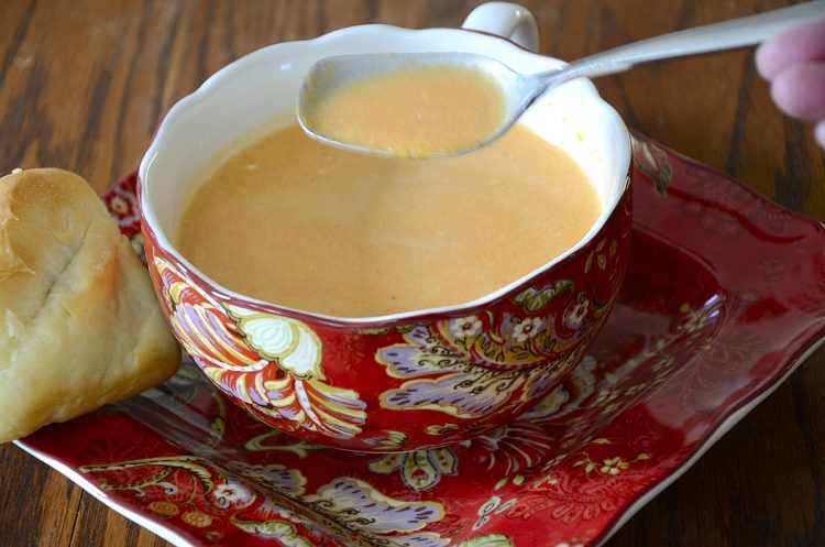 Creamy roasted red pepper soup in soup cup.