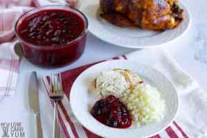 Canberry Blueberry sauce in a cup and on a plate beside a slice of turkey.
