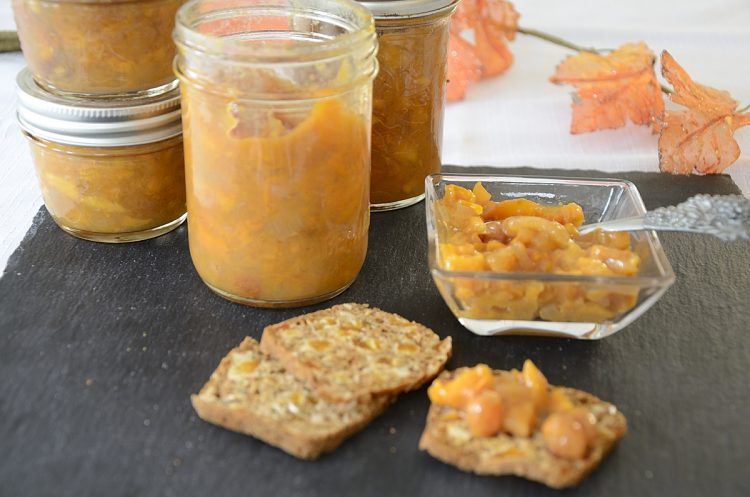Persimmon chutney on an Artisanal cracker with jars of chutney in the background.