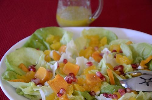 Salad on a platter with persimmons, mandarins and pomegranate seeds.