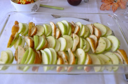 Slices of apples and pears in a baking pan tossed in olive oil and minced rosemary.