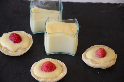 Tarts shells filled with lemon custard and topped with a fresh raspberry.  Small serving cups of lemon custard on the side.